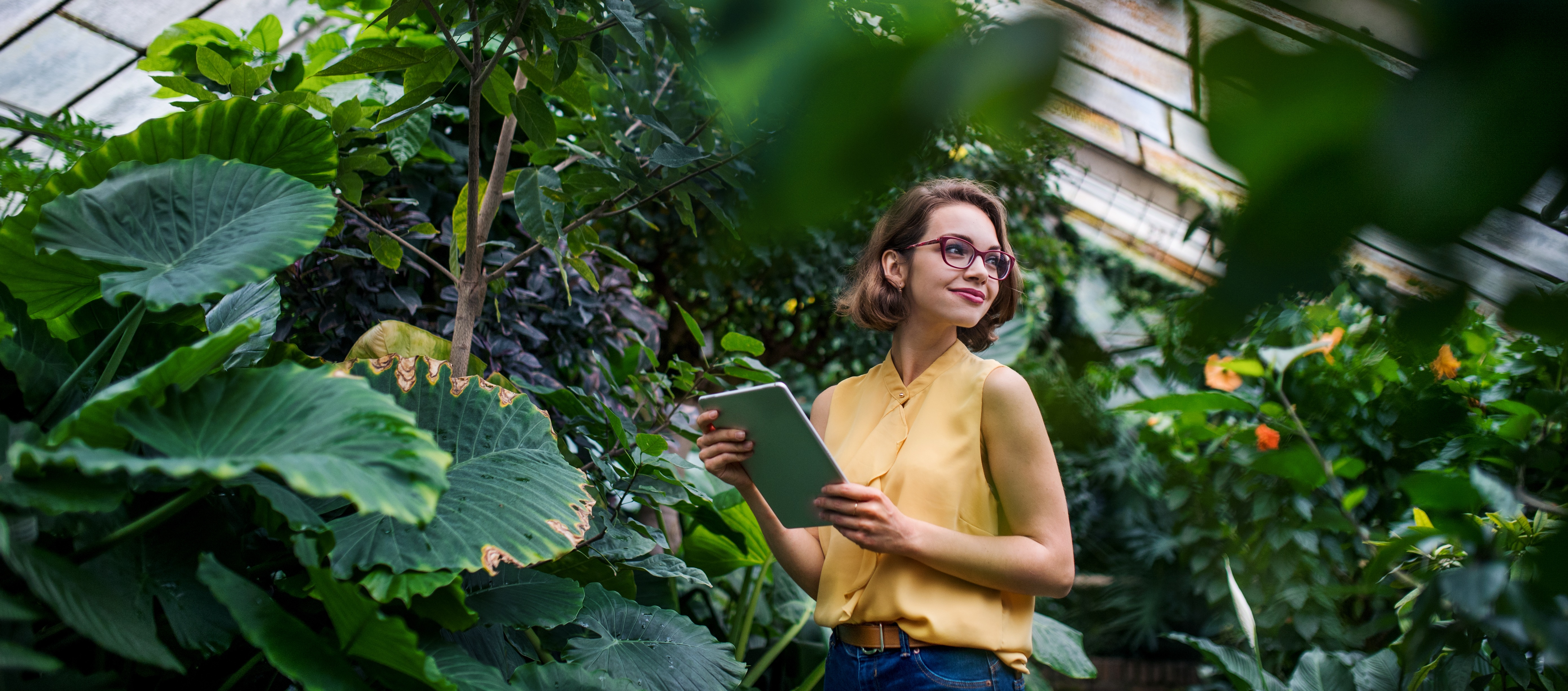 young-woman-with-tablet-standing-in-botanical-gard-UPDLYCT-2